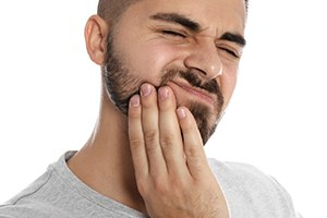 person with a toothache holding their mouth in pain