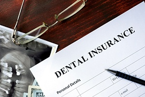 blank dental insurance form with X-rays laying underneath