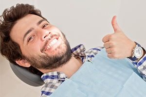 Man reclined in dental chair with thumbs up
