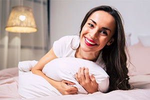 A woman hugging a pillow and smiling while in bed