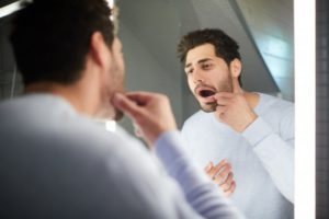 person examining their teeth in a bathroom mirror