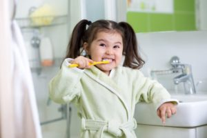 a child smiling and brushing their teeth in the bathroom