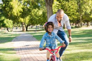 a child learning how to ride a bike with their parent