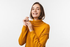 a person with braces smiling and wearing a yellow turtleneck sweater