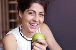a person who has braces smiling and holding an apple