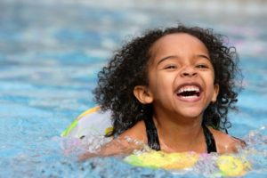 a child swimming in a pool and smiling