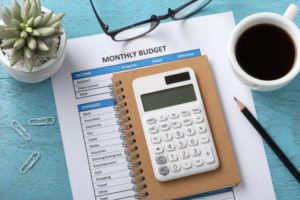 a calculator and monthly budget sheet next to a cup of coffee on a table