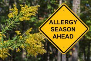 """a street sign that says """"allergy season ahead"""""""